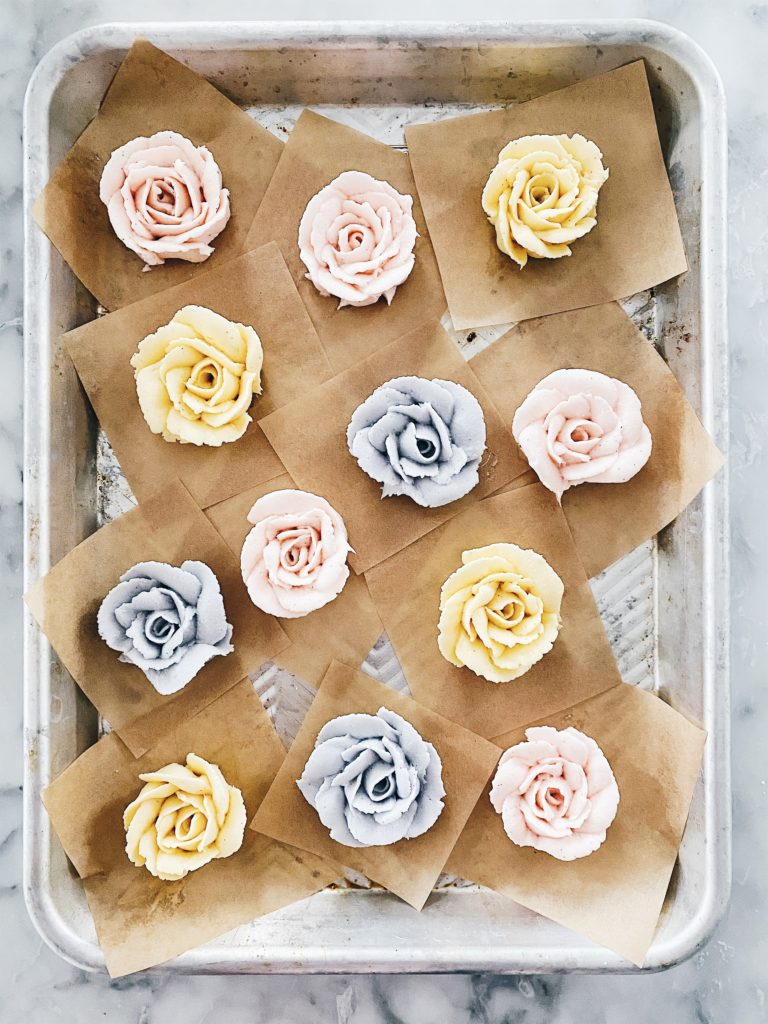 pastel colored buttercream roses on a baking sheet