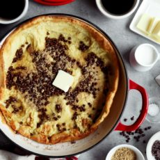 Freshly cooked Dutch baby sprinkled with chocolate chips and brown sugar