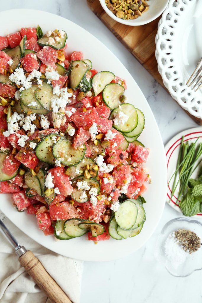 Easy watermelon salad tossed on an oval platter.